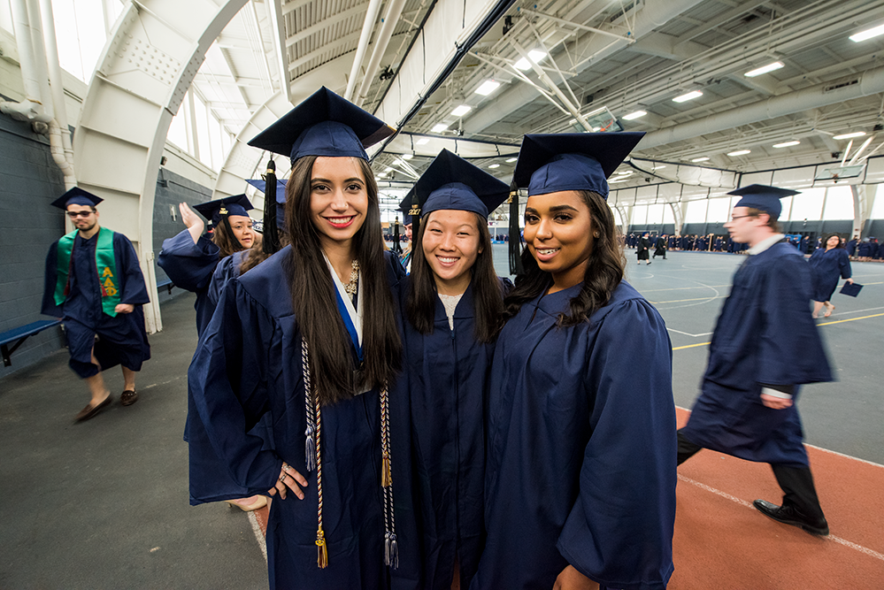 3 female friends wear new uconn graduation gowns
