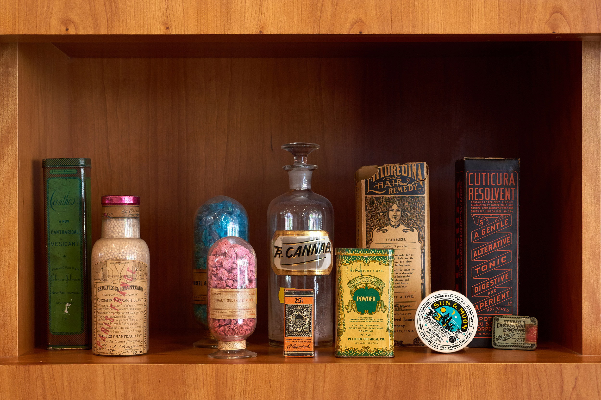 tintures and bottles sit inside a wooden cabinet