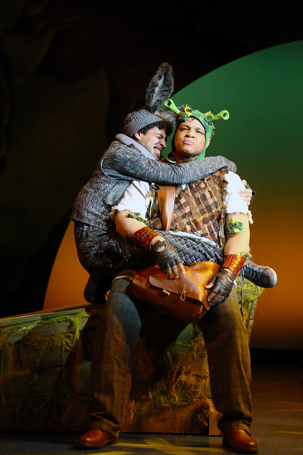 Donkey leaps into a begrudging Shrek's arms on the dimly lit stage