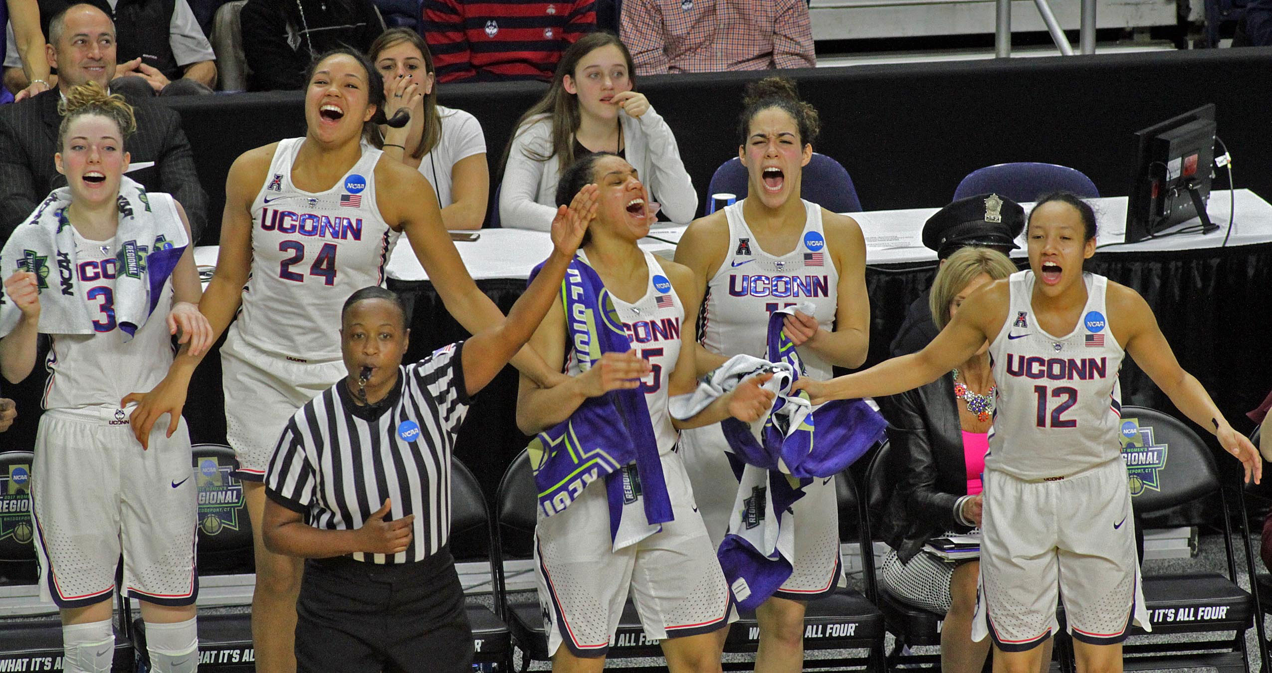 Group shot of UConn Women's Basketball team members cheering. From left:Katie Lou Samuelson '19 (CLAS), Napheesa Collier '19 (CLAS), Gabby Williams '18 (CLAS), Kia Nurse '18 (CLAS), and Saniya Chong '17 (CLAS) cheer on teammates (not pictured) Molly Bent '20 (ACES), Natalie Butler, Crystal Dangerfield '20 (ACES), Kyla Irwin '20 (CLAS), and Tierney Lawlor '17 (CAHNR) during their Elite Eight defeat of Oregon.