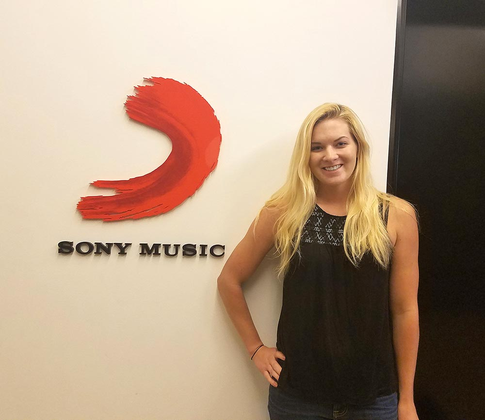 Maggie Quackenbush in front of Sony Music logo on wall