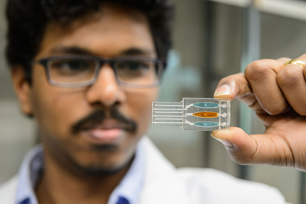 Postdoctoral researcher Karteek Kadimisetty holds the 3-D printed sample chamber of his genetic toxicity testing device. (Peter Morenus/UConn Photo)