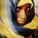 Image of a woman staring back at the viewer. She wears a headscarf of blue and yellow