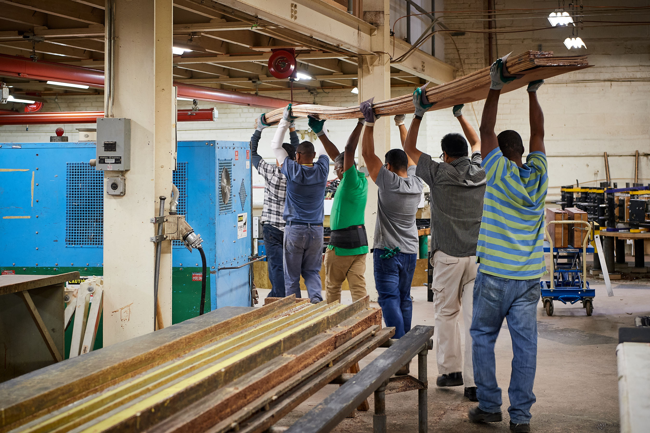 Craftsmen carry a laminate book of wood strips to a bending jig for forming a piano rim at the Steinway & Sons factory