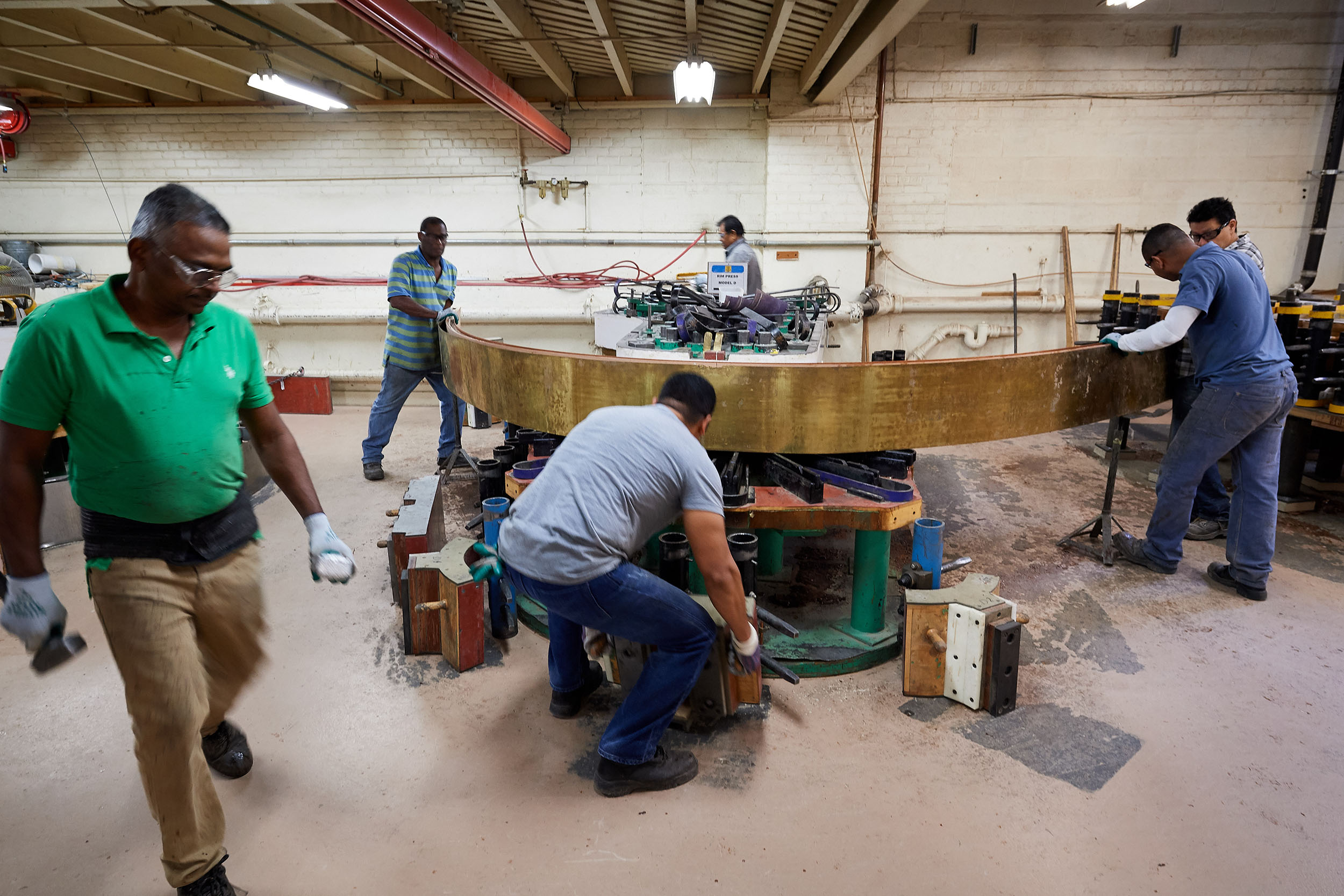 Craftsmen wrap the laminate around a piano rim bending jig at the Steinway & Sons factory
