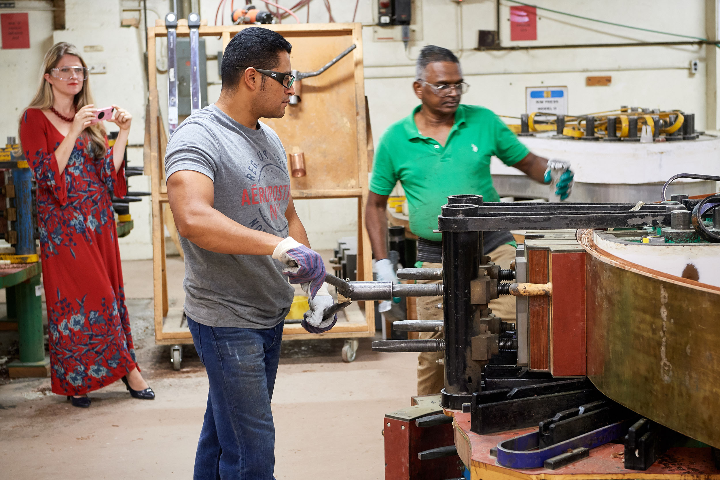 Angelina Gadeliya, assistant professor in Residence of Piano and coordinator of keyboard studies, left, photographs craftsmen forming a piano rim at the Steinway & Sons factory