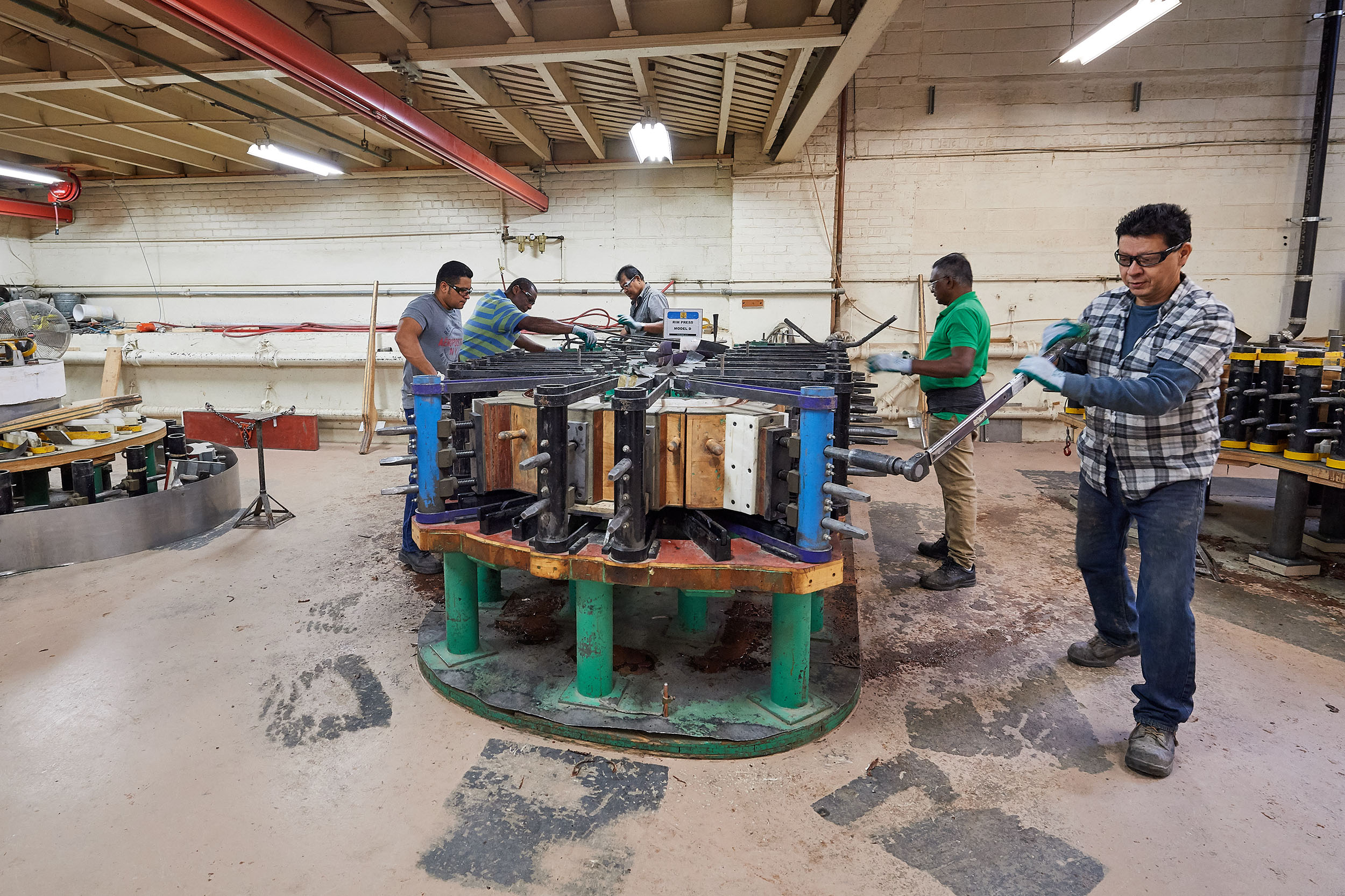 Craftsmen tighten a jig to form a piano rim at the Steinway & Sons factory