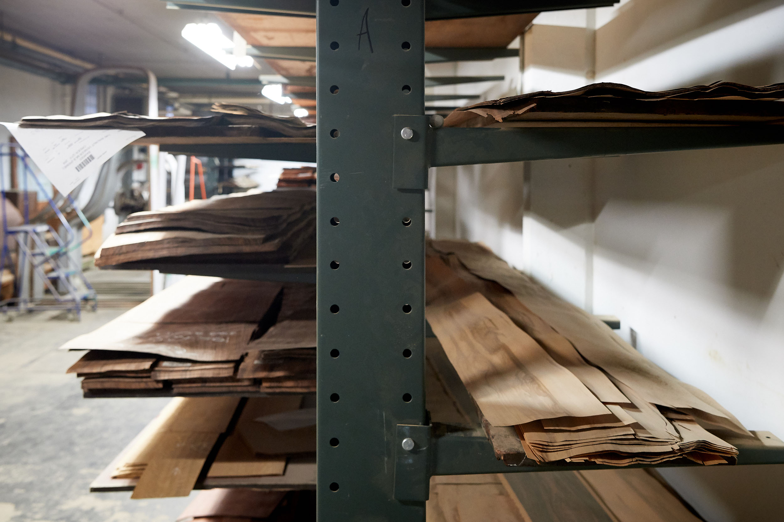 Stacks of fine wood laminate on a rack at the Steinway & Sons factory