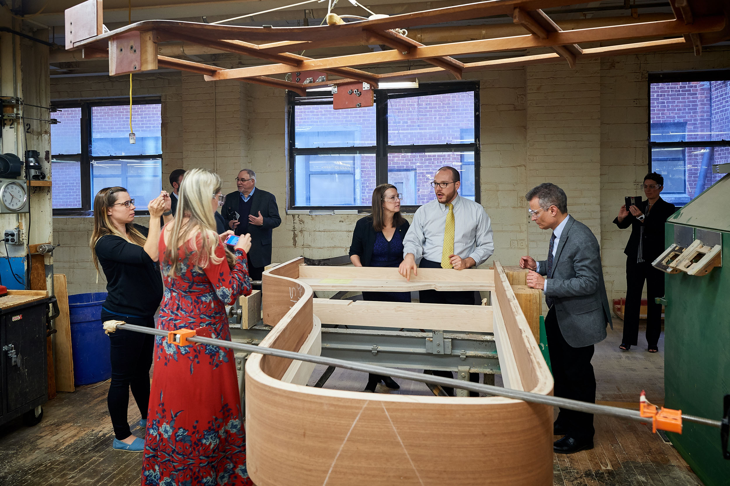Logan Thompson, selection room manager, shows a tour group a Steinway & Sons piano under construction