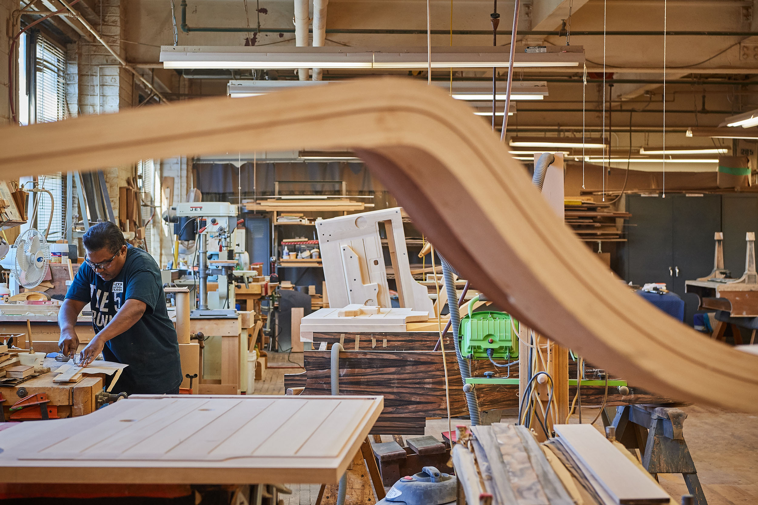 A craftsman cuts laminate before gluing it to a piano at the Steinway & Sons factory