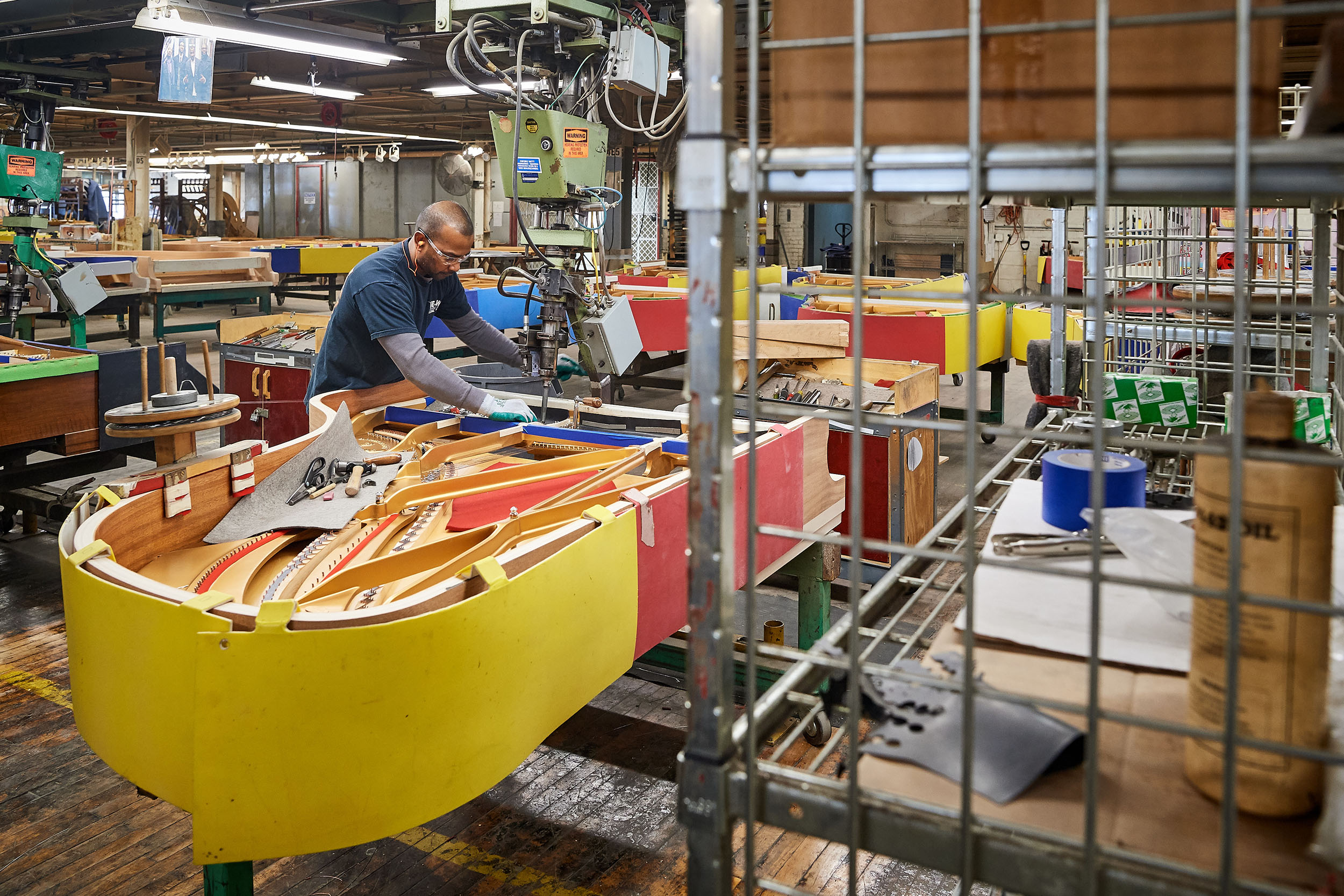 A craftsman installs piano strings at the Steinway & Sons factory