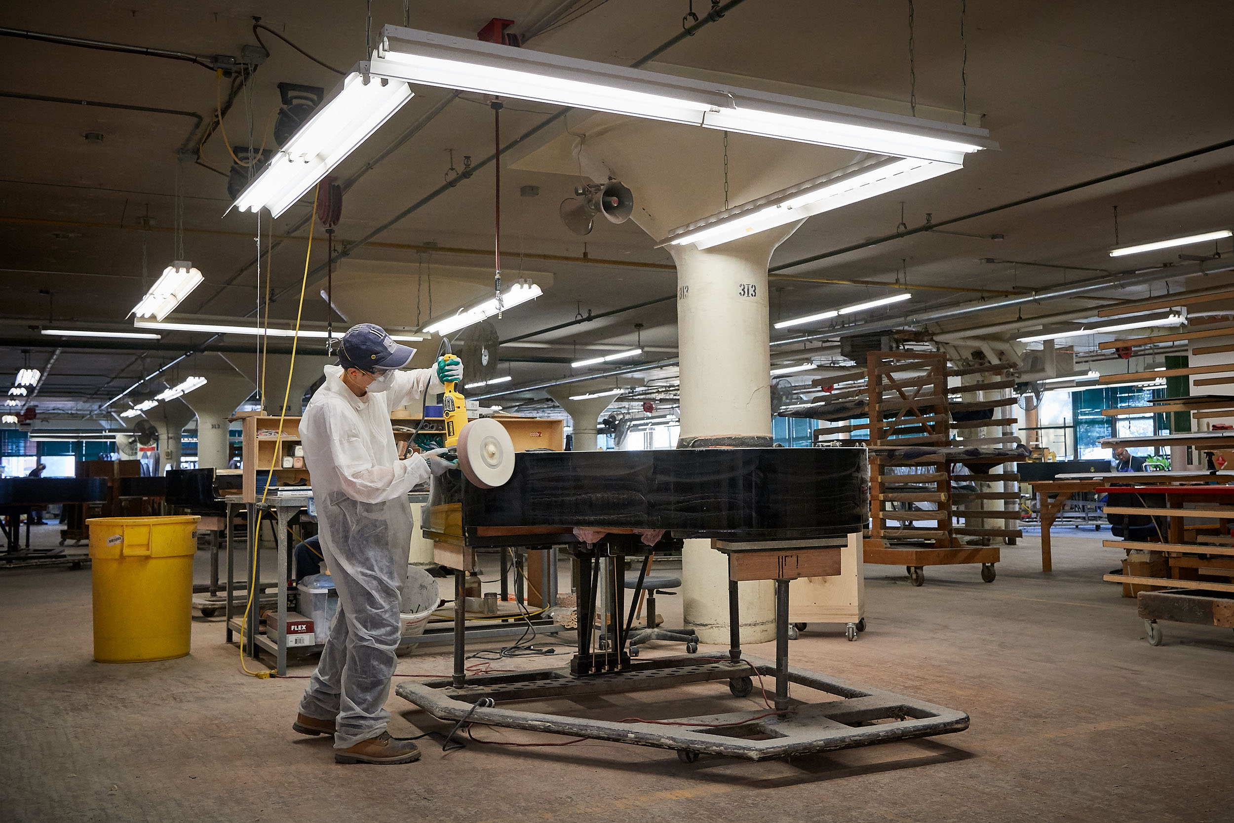 A craftsman polishes a Steinway & Sons piano at the factory