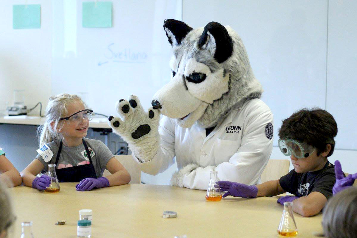 Jonathan the husky (mascot) and children do science experiments at UConn's Science Salon Jr. Event
