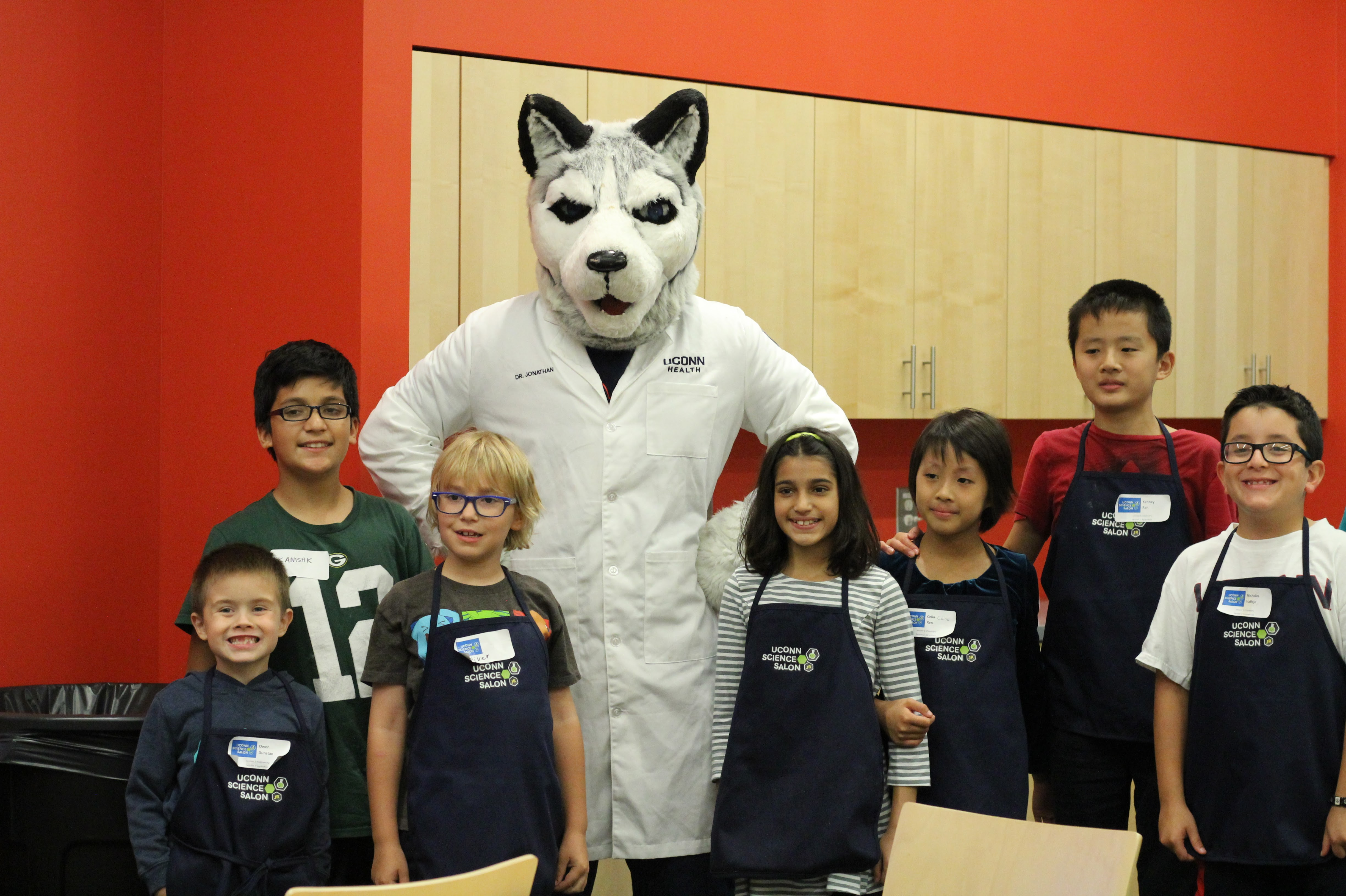 Jonathan, the husky (mascot), takes a photo with Science Salon Jr. children