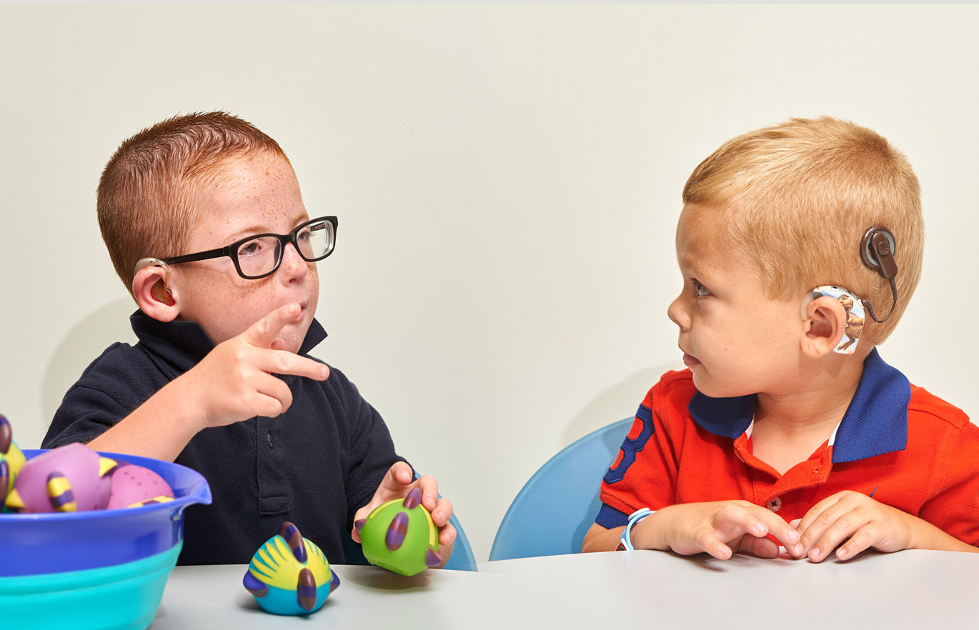 Two children looking at each other doing sign language