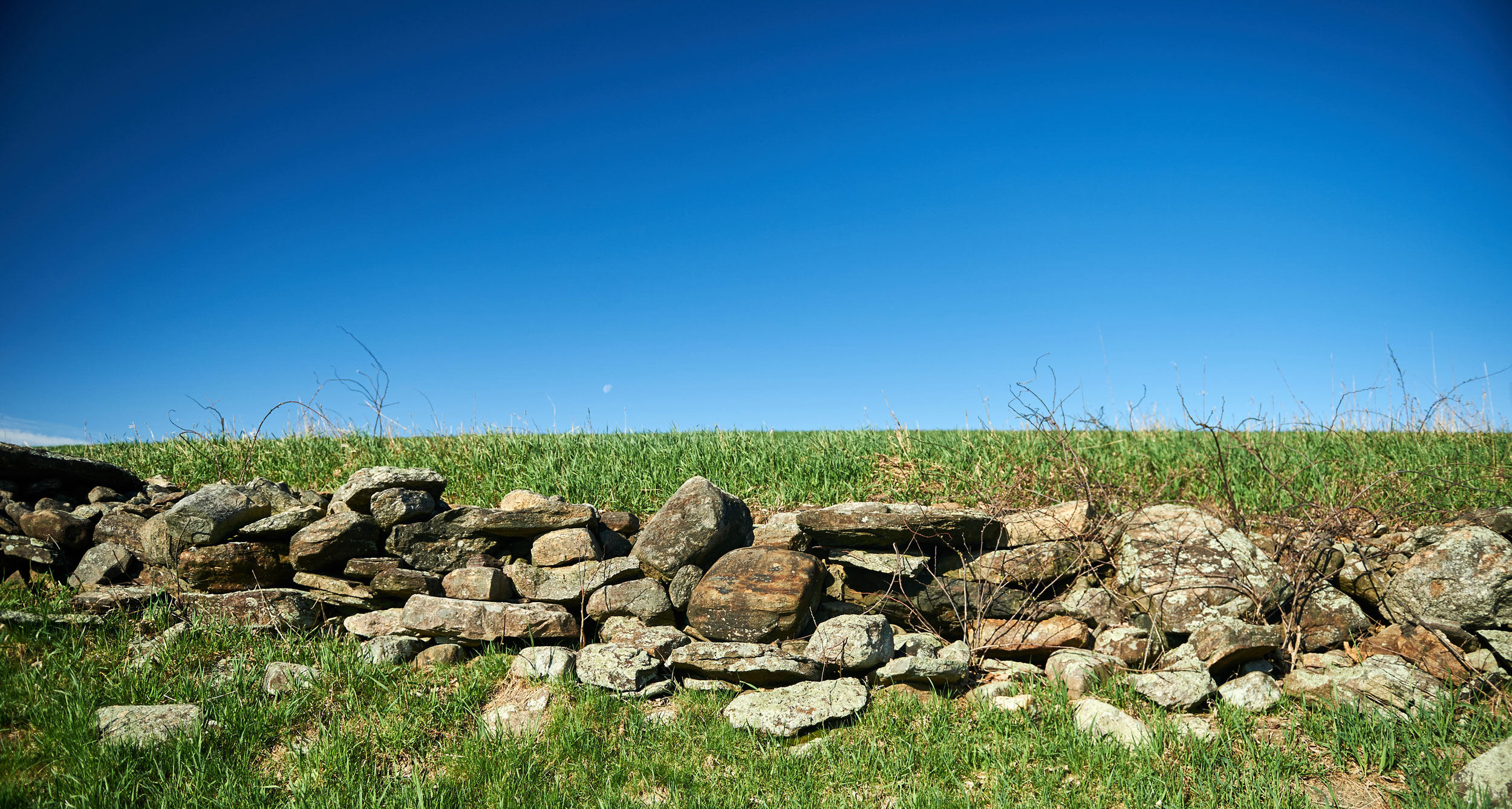 Rock wall in the foreground with bright blue skies