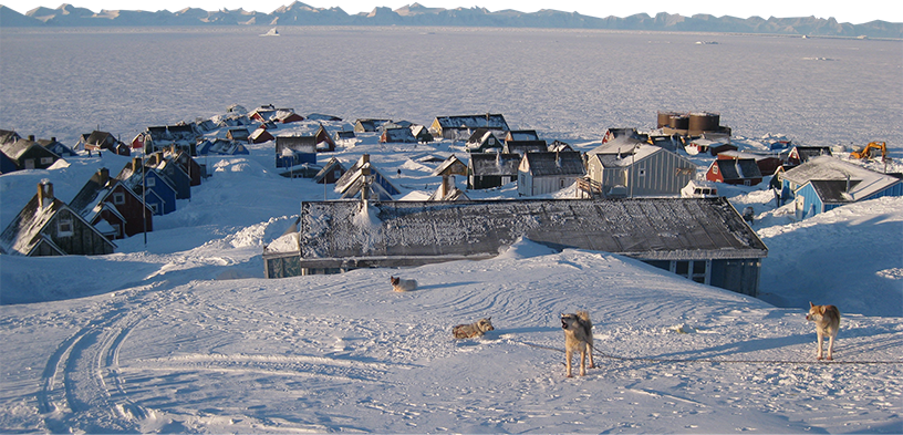 a snow covered research station in Greenland. It's surrounded by vast tundra. Huskies howl in the foreground