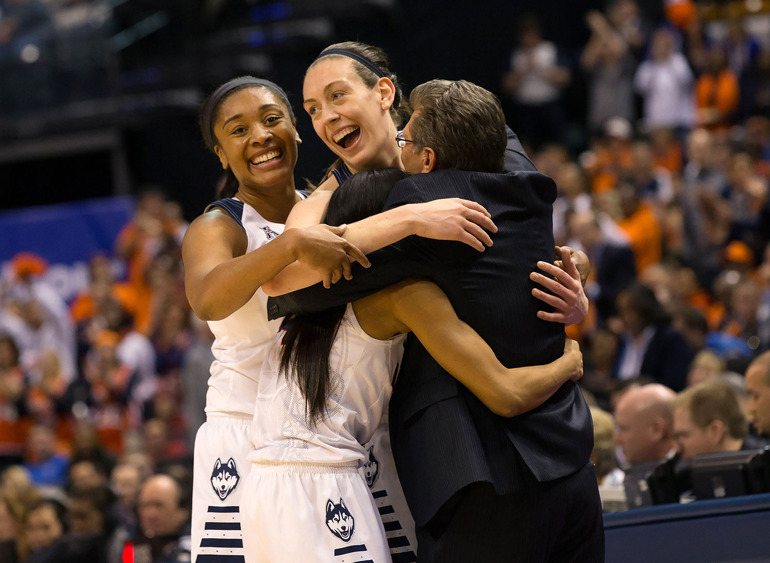 Geno Auriemma embraces UConn women's team players, Stewie, Mo, and Tuck, after 2016 championship win