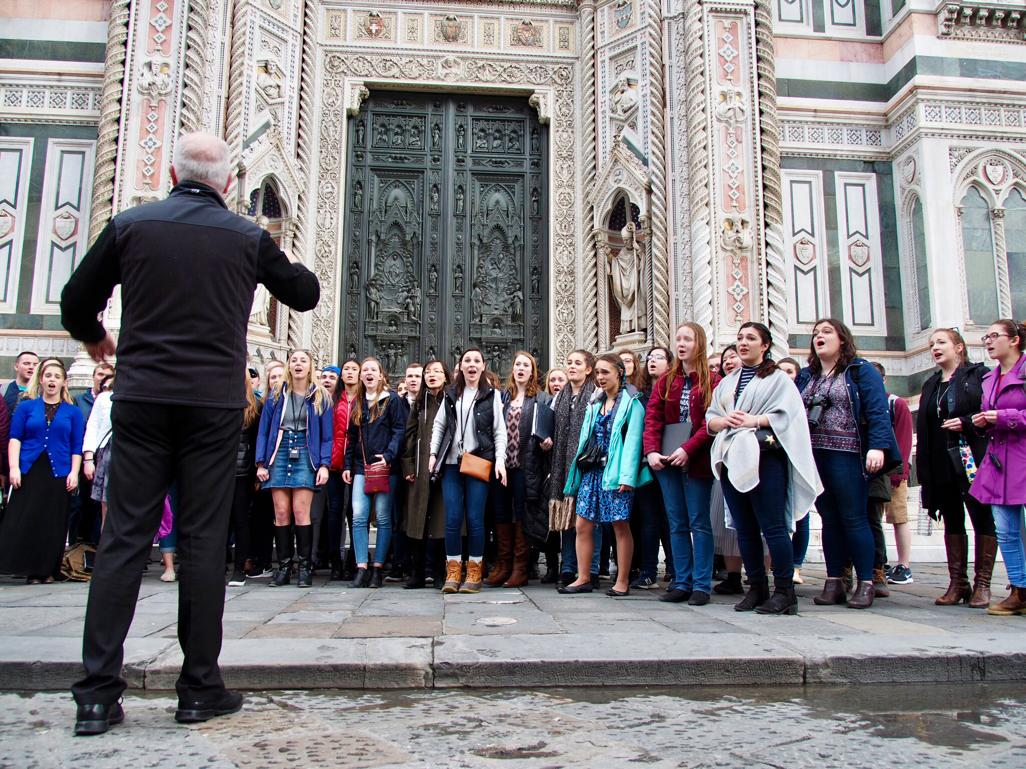 "Jamie Spillane '87 MM, associate professor of music and director of choral studies, directs UConn's Concert Choir singing ""Unclouded Day"" in front of the Florence Cathedral"