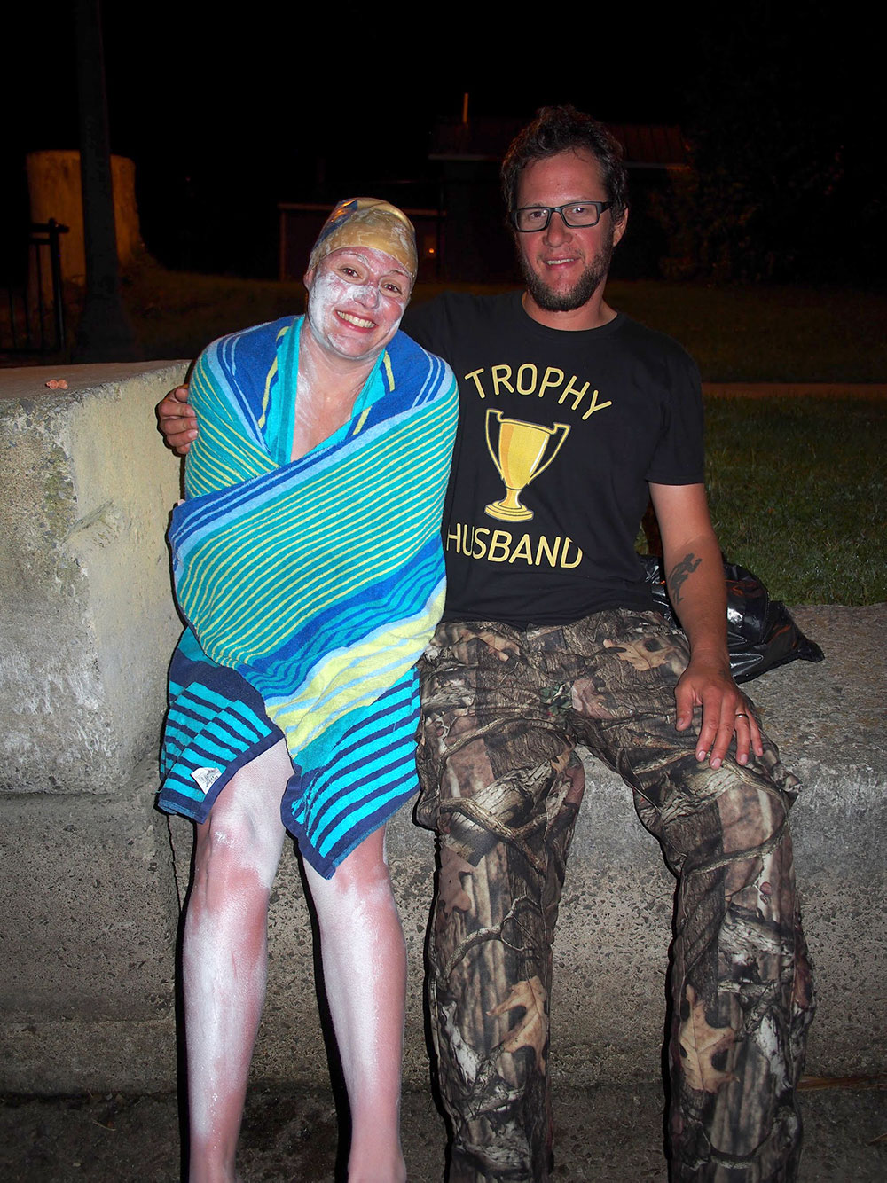 Sarah Thomas, covered in heavy-duty sunscreen, after her world-record–breaking marathon swim across Lake Champlain, stands next to her husband, who is wearing a shirt saying 'trophy husband'
