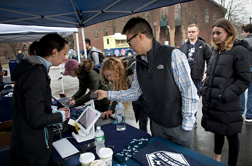 People giving at a donation table for UConn Gives