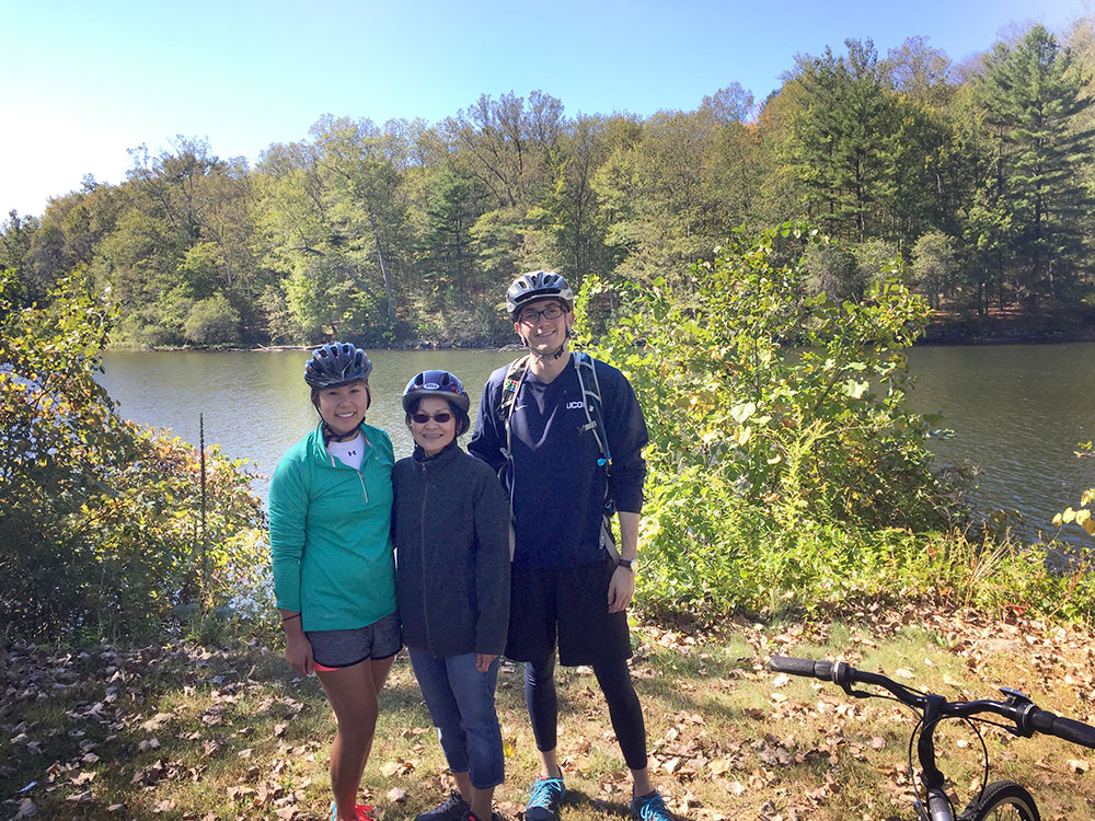 "Then pharmacy graduate students Celeste Cheung '18 Pharm.D. (left) and Connor Walker '18 Pharm.D. (right) during a 20-mile bike ride along the Farmington River last year with their patient, friend, and ""Cambodian mom"" Lila Plawecki."