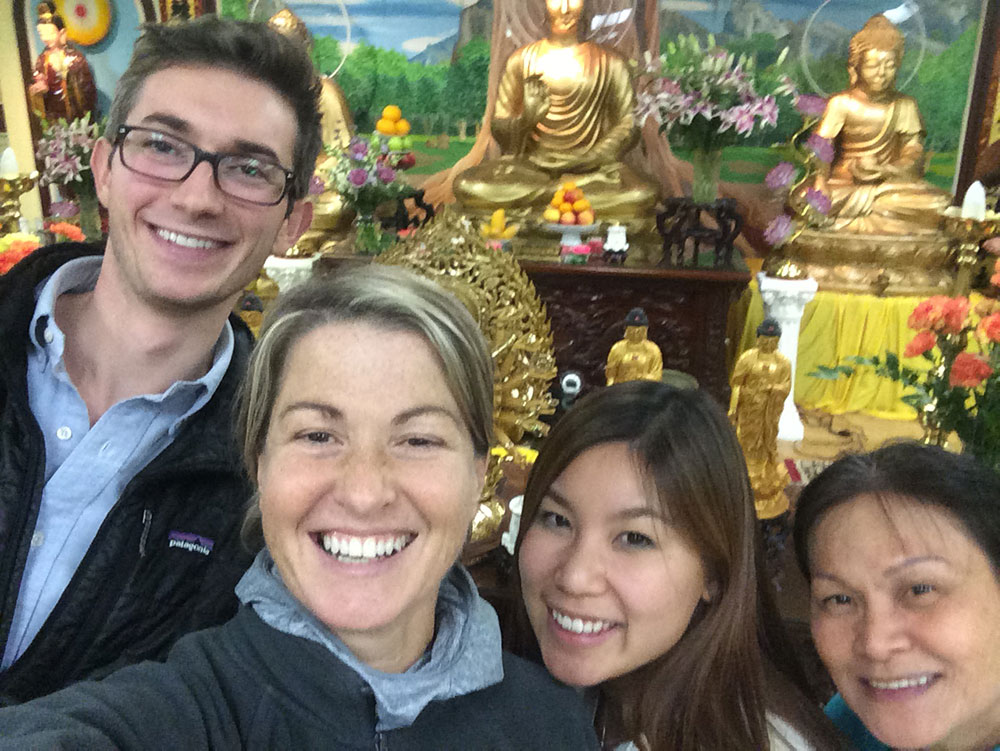 four people stand in front of an ornate Vietnamese temple
