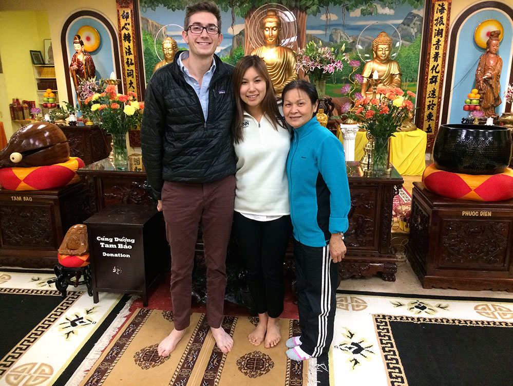 "then pharmacy graduate students Connor Walker '18 Pharm.D. and Celeste Cheung '18 Pharm.D. at the Hai An Pagoda Vietnamese temple with their patient, friend, and ""Cambodian mom"" Lila Plawecki"