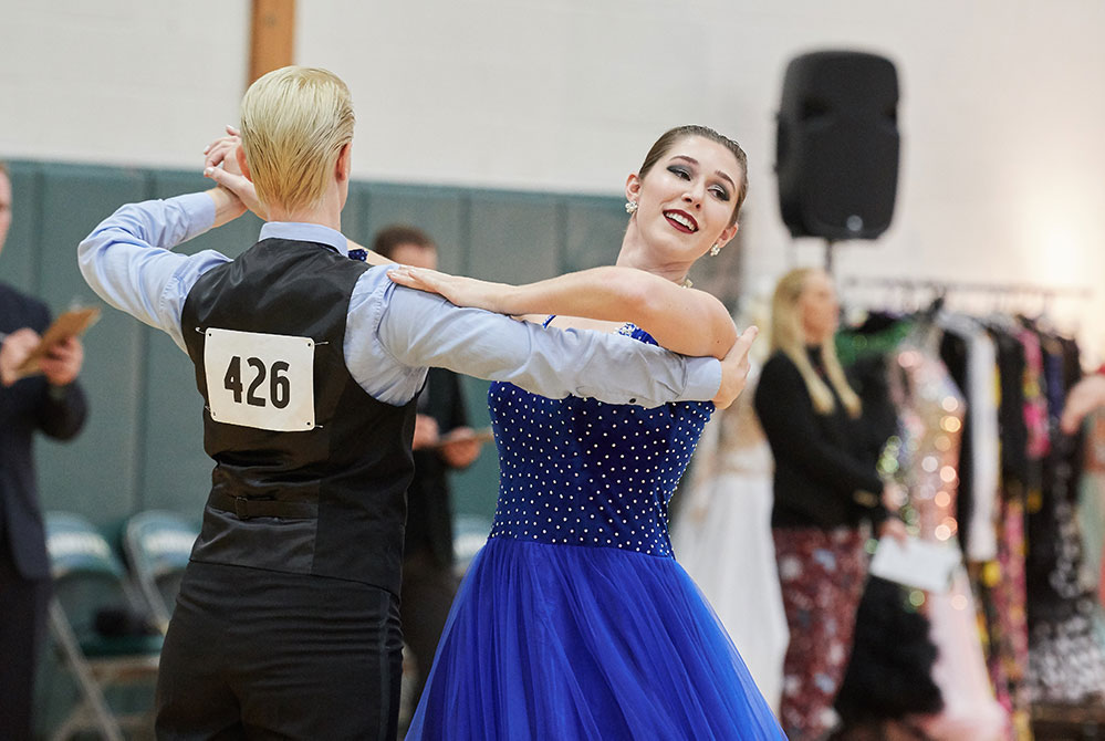 student ballroom club member all female couple dance. A woman in a blue dress faces the camera