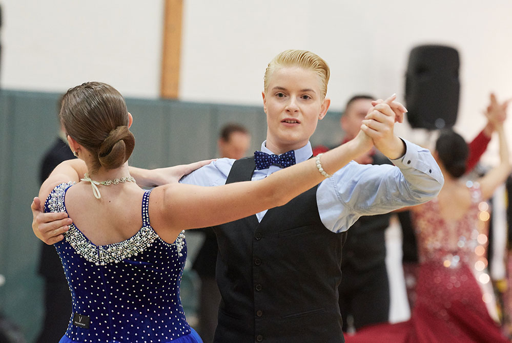 student ballroom club member all female couple dance. A woman in a black suit faces the camera