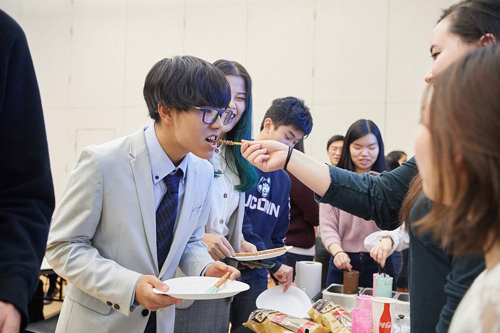 JSA student club member eats a chocolate covered pretzel stick