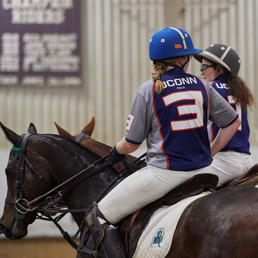 UConn club member plays polo on a black horse