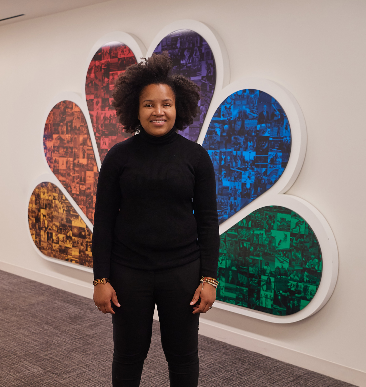 Naika Denerville stands near an NBC peacock logo at NBC Sports Group in Stamford