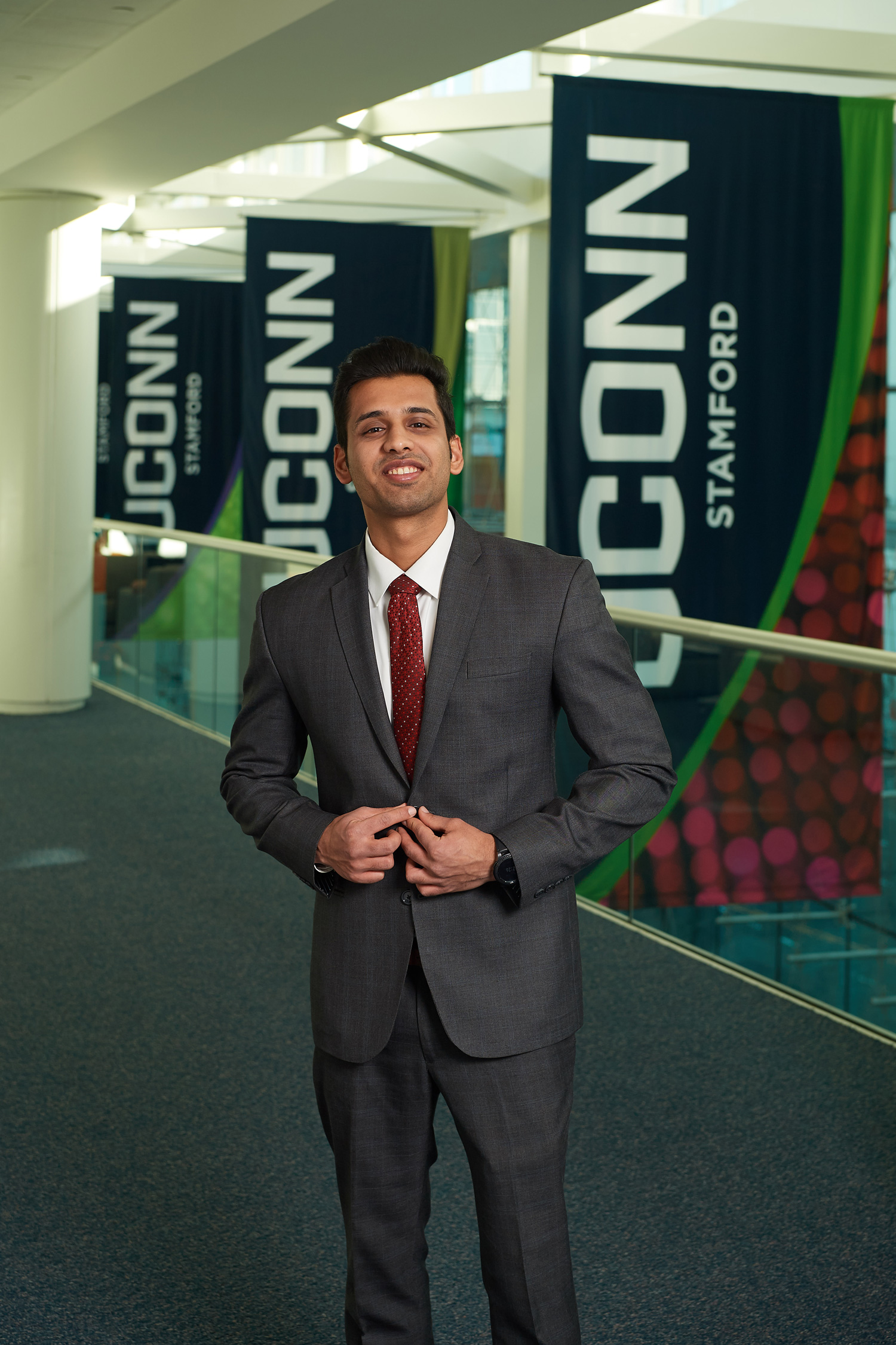 Anshul Maglani stands near the flags hanging in the Stamford campus atrium