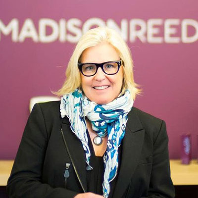 Amy Errett in front off a madison reed sign