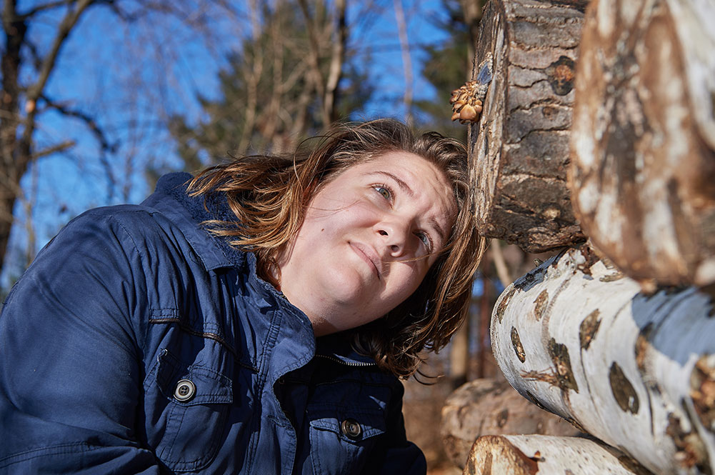 woman inspects mushroom species