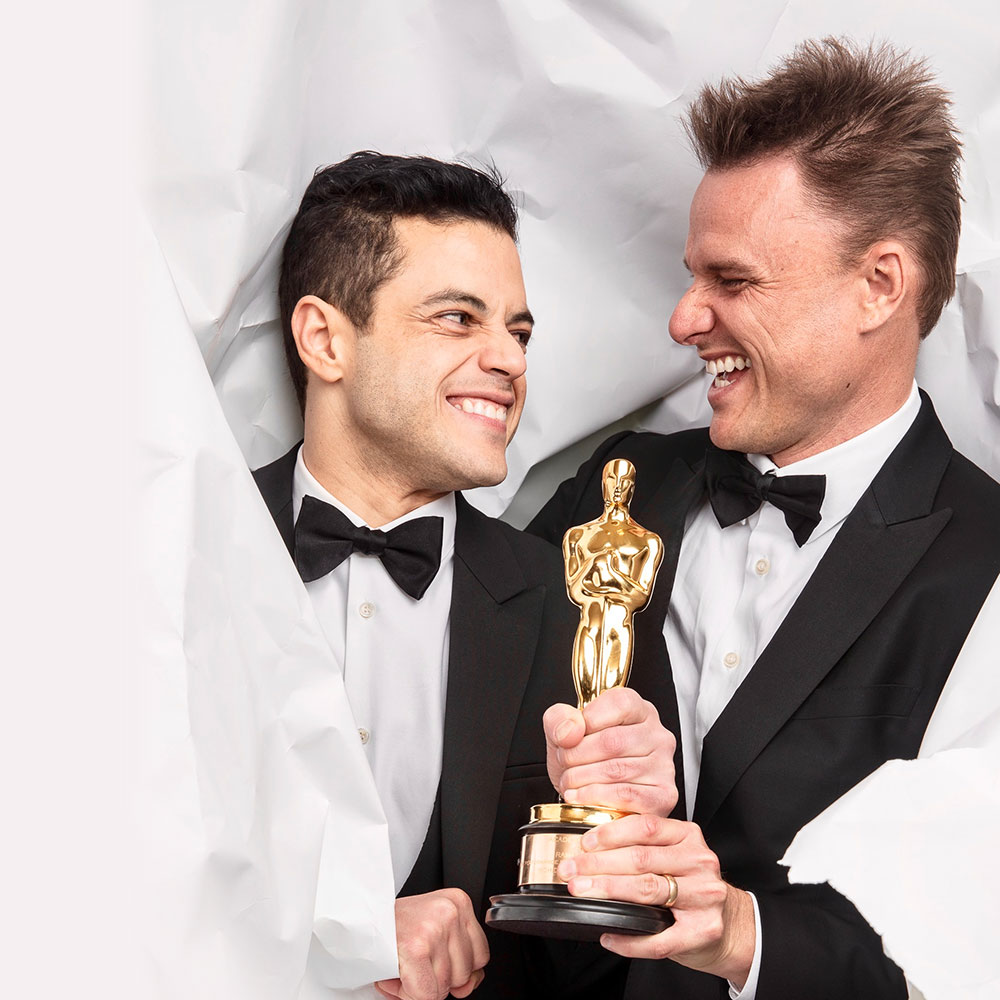 Curtis (right) with Malek, aka Freddie Mercury. holding an Oscar