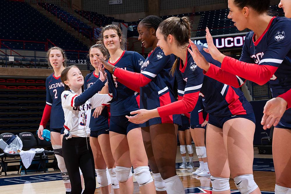 Elsa hi-fiving UConn Women's Volleyball Team