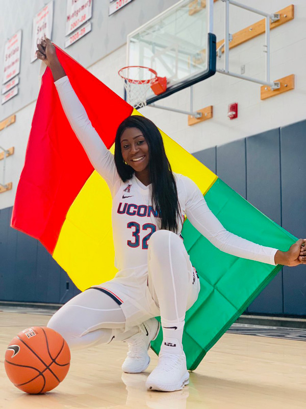 Batouly Camara in her UConn uniform holding the Guinea flag