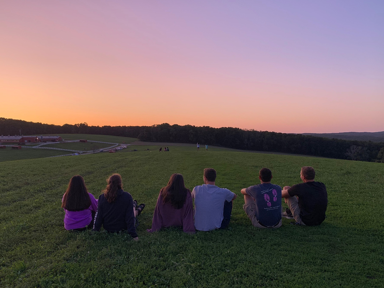 students stare out into a sunset on Horsebarn Hill in UConn Storrs campus