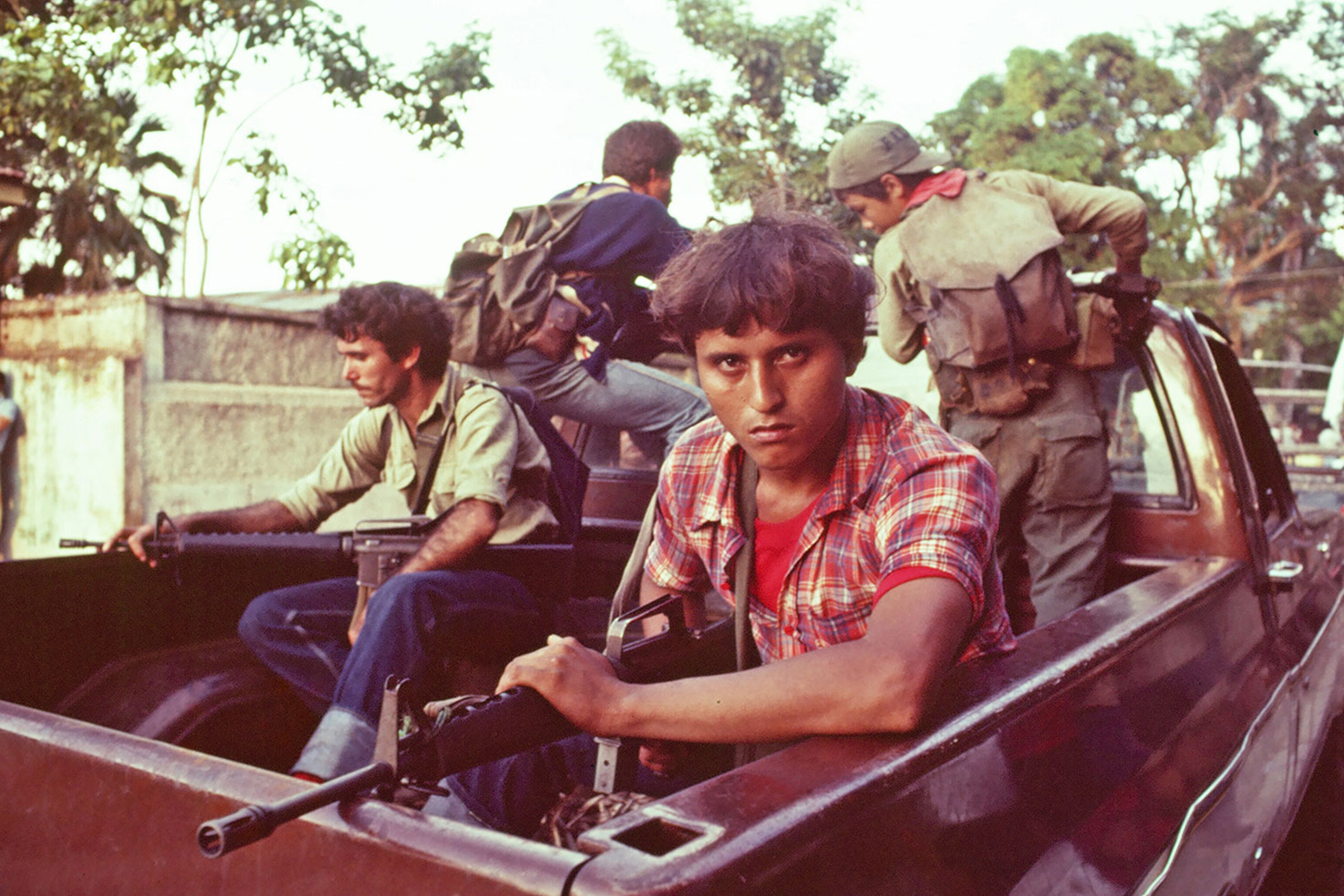 Leftist rebels enter the city of Chinameca, El Salvador, aboard a pickup, 1983.