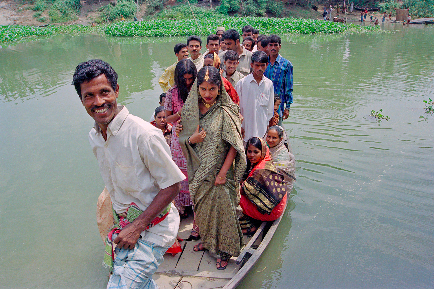 Boatman brings wedding party to riverbank in Narayanganj, Bangladesh, 2004.