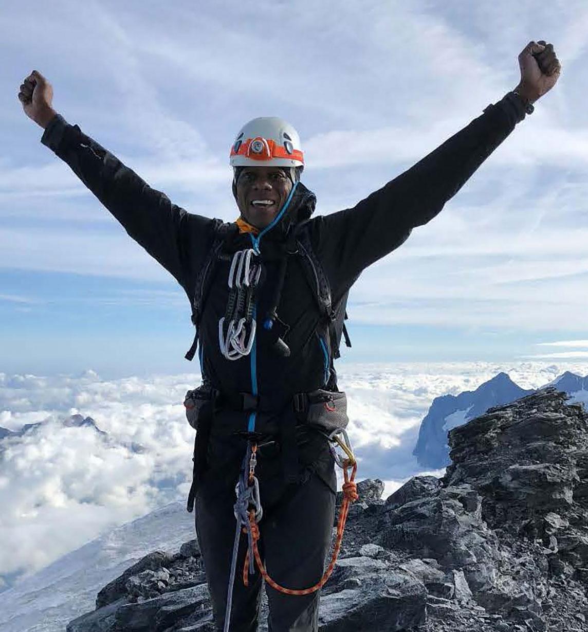 Rohan Freeman celebrating atop a mountain peek
