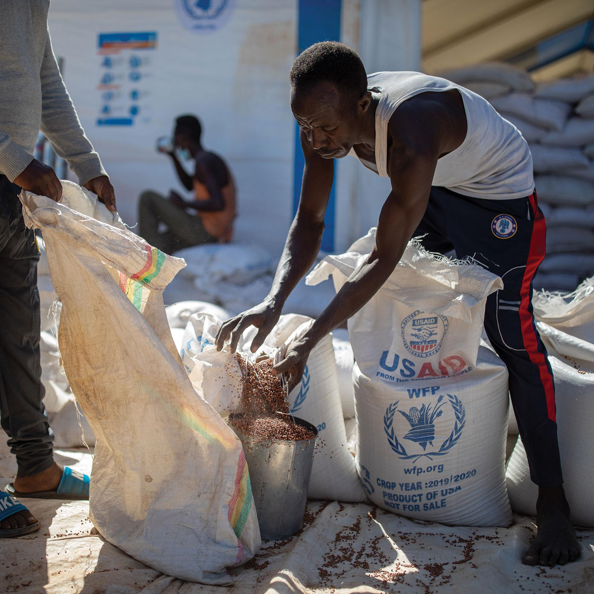 WFP transporters distribute sorghum to refugees in Um Rakuba camp in eastern Sudan.