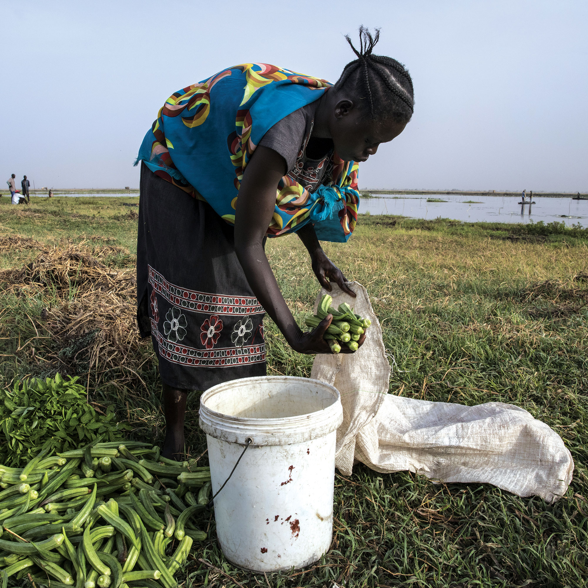 Akon Garang, 27, washes vegetables from her garden in South Sudan where WFP programs involve the community in planning and creating crop farms, vegetable gardens, and access roads.