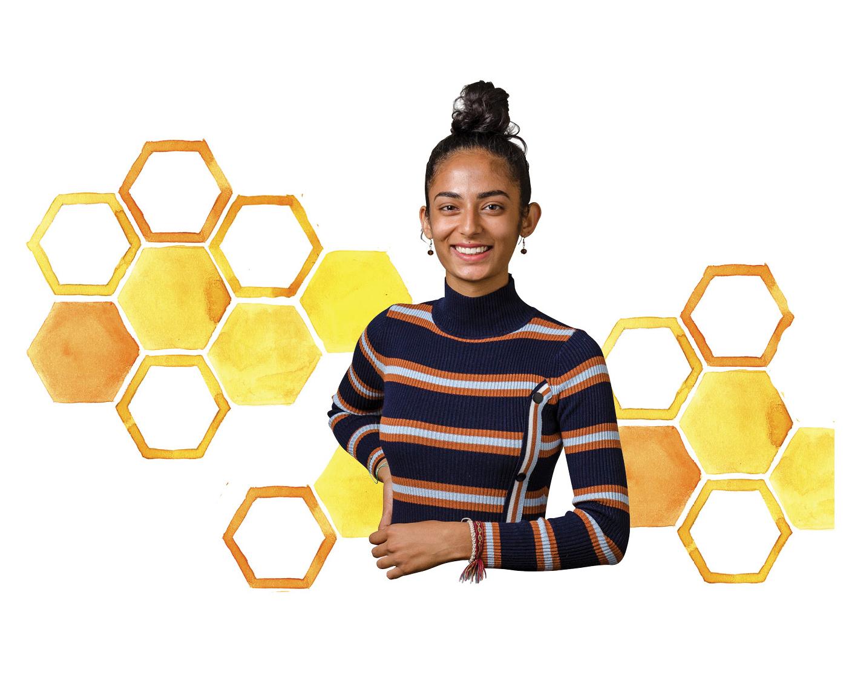 Raina Jain posing in front of a honeycomb watercolor pattern