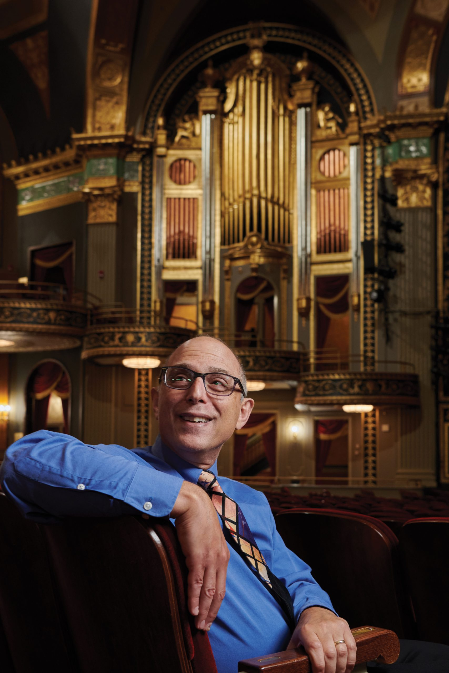 Stuart Brown leands over, smiling, at the Palace Theater in