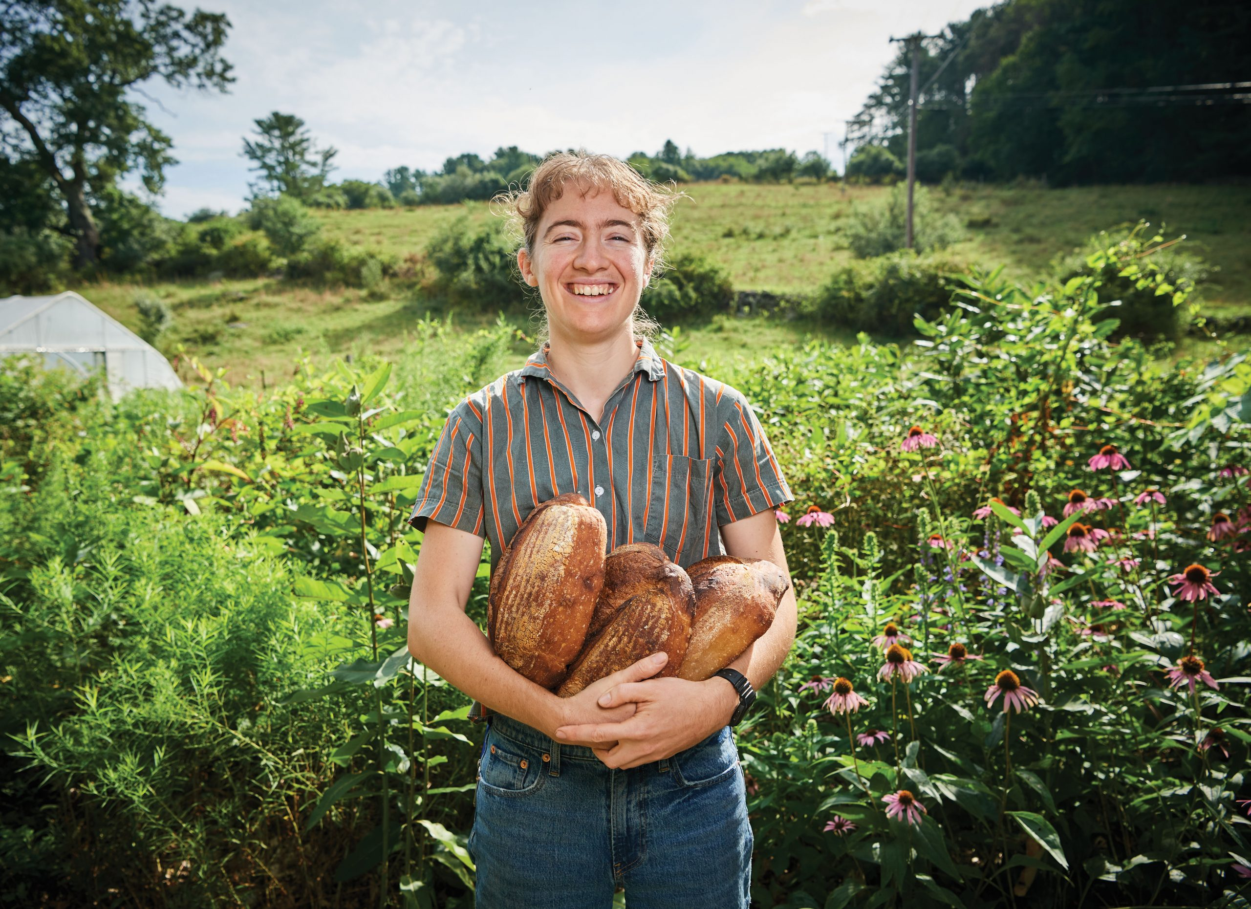 Jessica Larkin-Wells smiling broadly and holding loaves of sourdough bread while standing outdoors at Spring Valley Student Farm