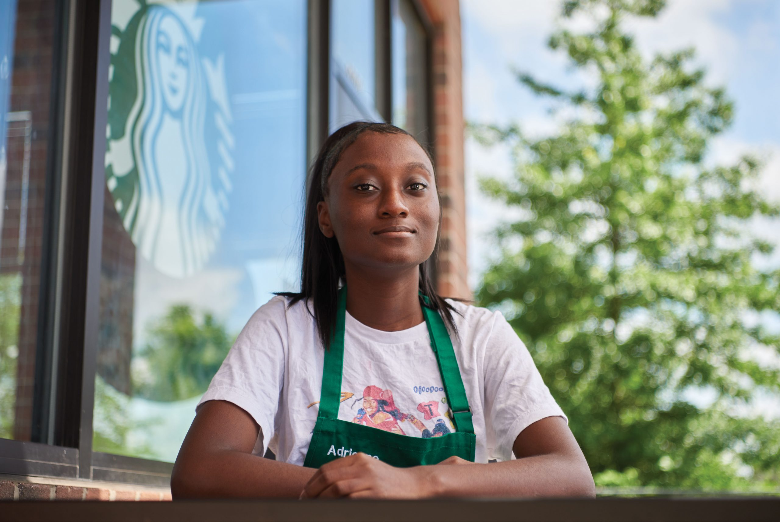 Adrienne Bruce sits at a table outside Starbucks