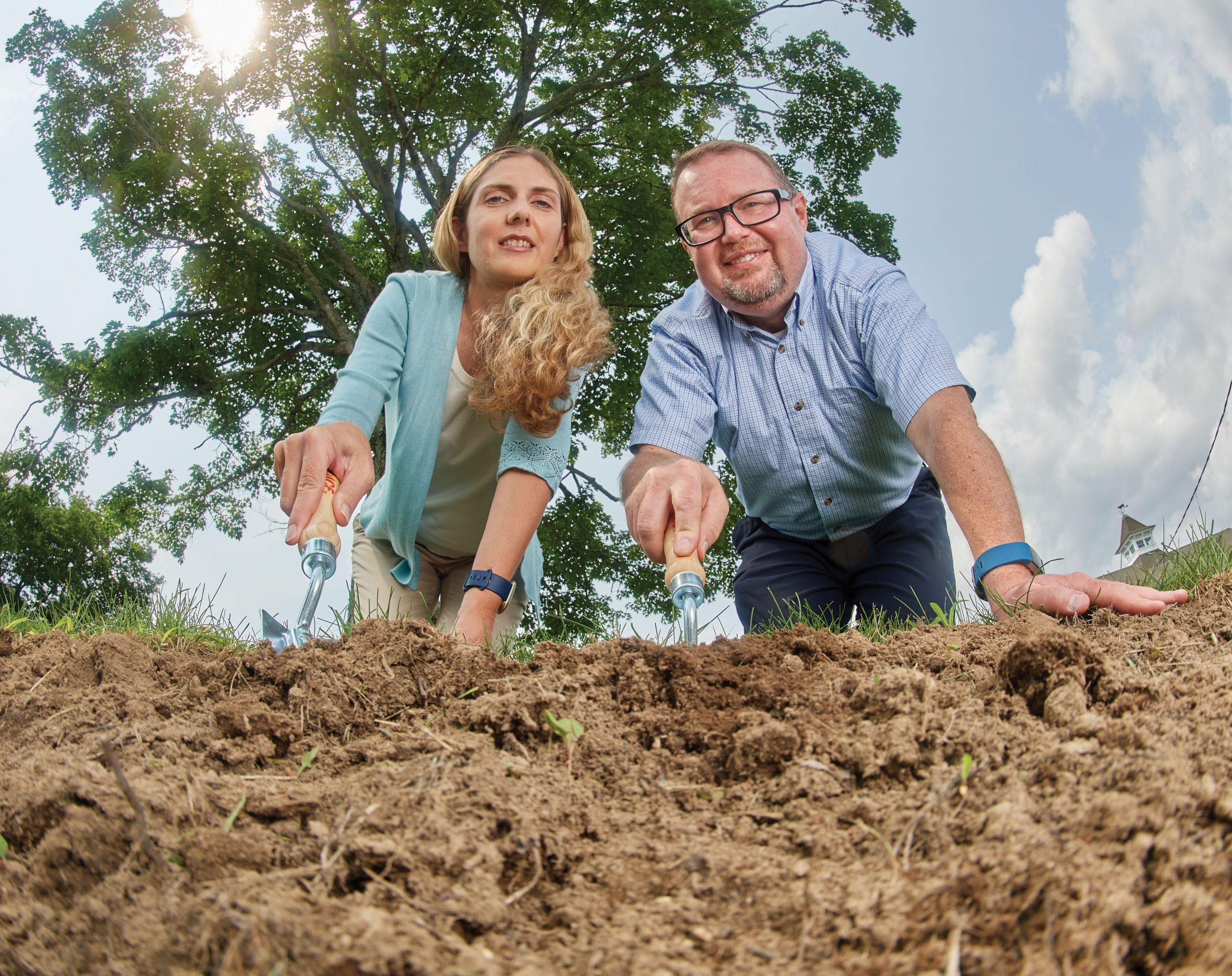 Worm's eye view of Patricia Rossi, left, assistant professor in residence of molecular science and cellular biology, and Spencer Nyholm, associate professor of molecular science and cellular biology, digging dirt